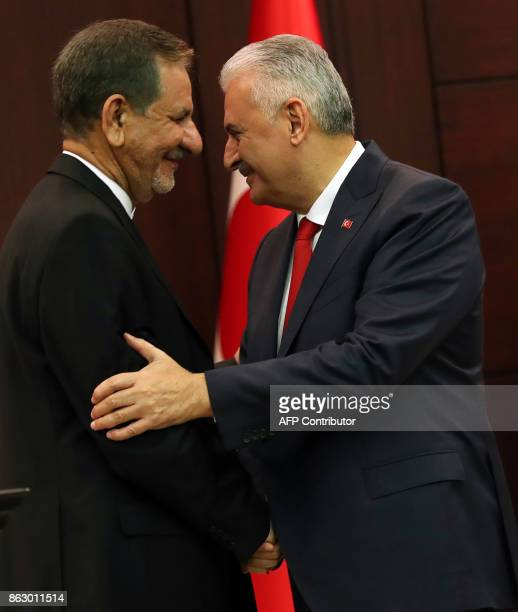 Turkish Prime Minister Binali Yildirim and Iran's First Vice President Eshaq Jahangiri shake hands as they hold a joint press conference at Cankaya...