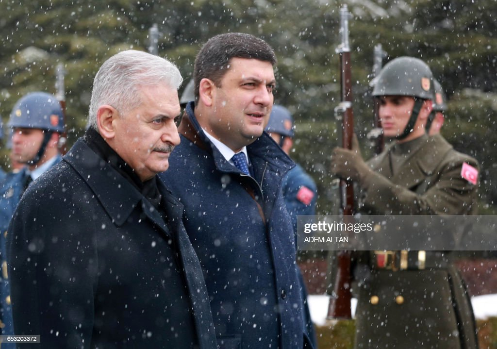 Turkish Prime Minister Binali Yildirim (L) and Prime Minister of Ukraine Volodymyr Groysman (R) walk past honor guards during a welcoming ceremony at the Cankaya Palace in Ankara, on March 14, 2017. /