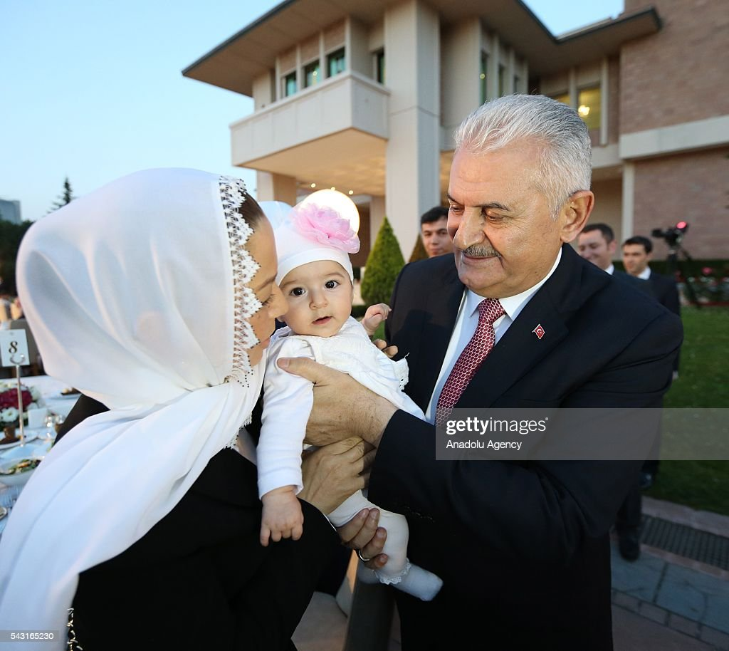 Turkish Prime Minister Binali Yildirim hugs a baby as he attends an Iftar (fast-breaking) Dinner with martyr families during Islamic holy month Ramadan at the Cankaya Mansion in Ankara, Turkey on June 26, 2016.