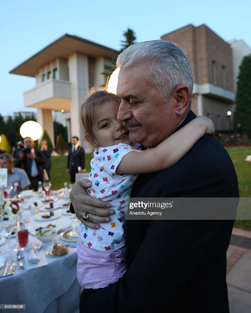 Turkish Prime Minister Binali Yildirim hugs a child as he attends an Iftar (fast-breaking) Dinner with martyr families during Islamic holy month Ramadan at the Cankaya Mansion in Ankara, Turkey on June 26, 2016.