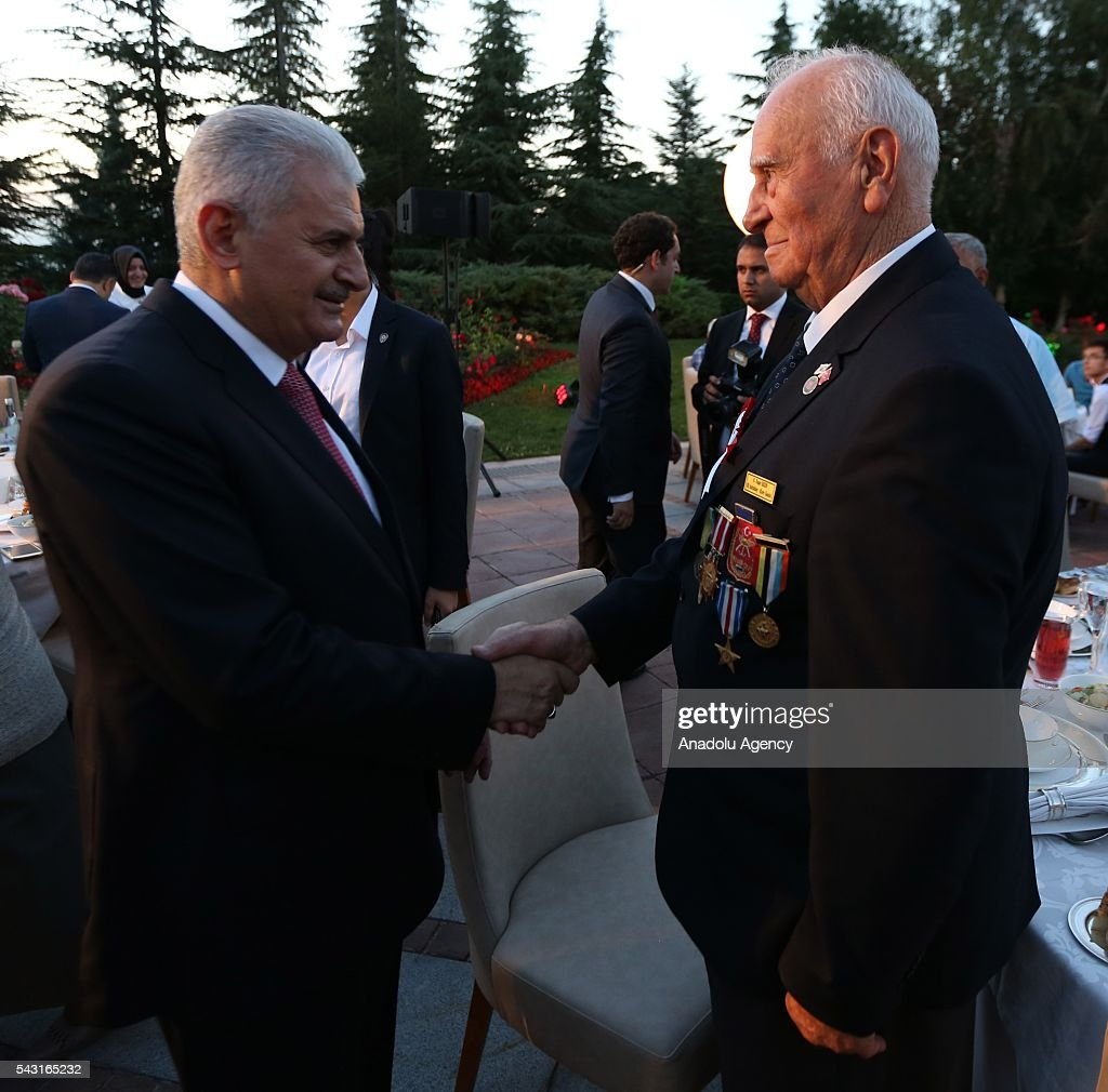 Turkish Prime Minister Binali Yildirim (L) shakes hand with a guest as he attends an Iftar (fast-breaking) Dinner with martyr families during Islamic holy month Ramadan at the Cankaya Mansion in Ankara, Turkey on June 26, 2016.