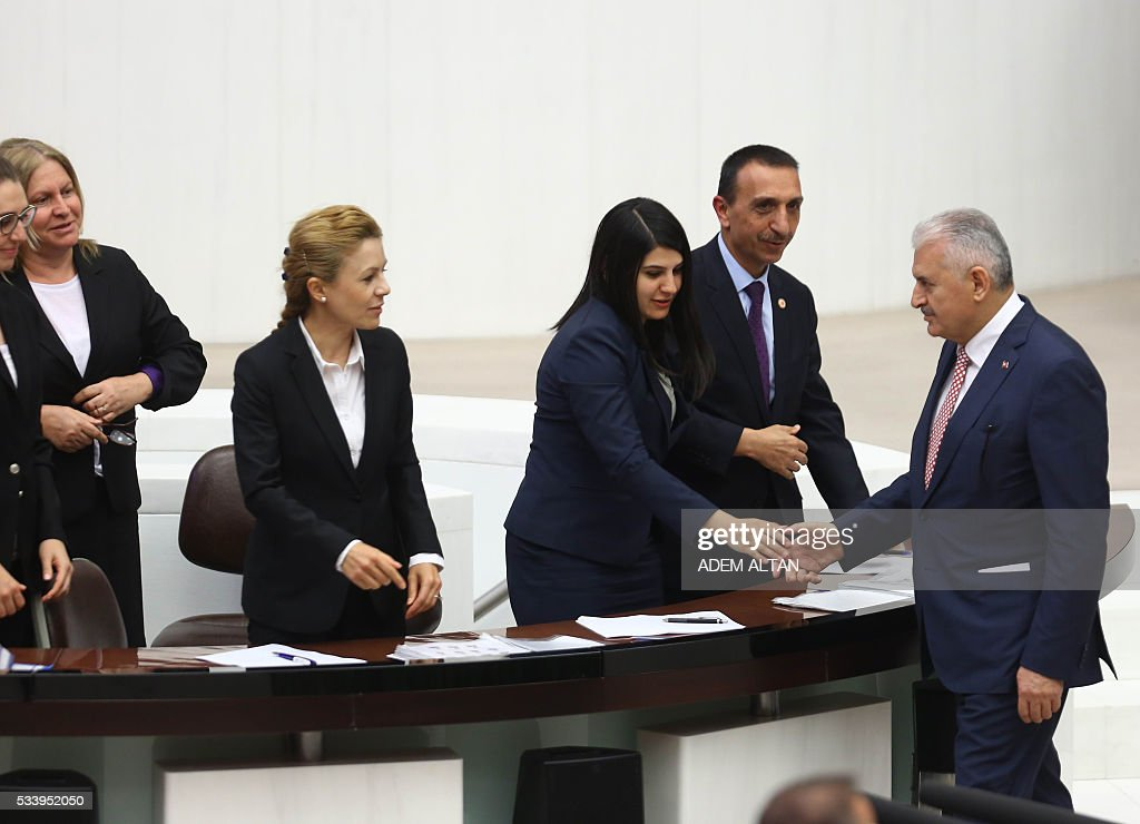 Turkish Prime Minister Binali Yildirim (R) shakes hands with the stenographers after presenting Turkeys 65th government's program to the Grand National Assembly of Turkey (TBMM) in Ankara, on May 24, 2016. / AFP / ADEM