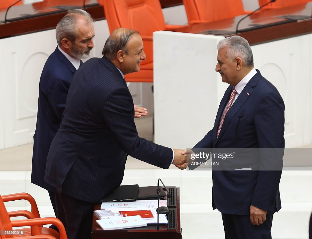 Turkish Prime Minister Binali Yildirim (R) shakes hands with the Turkish Nationalist Movement Party (MHP) Group Deputy Chairman Oktay Vural after presenting Turkeys 65th government's program to the Grand National Assembly of Turkey (TBMM) in Ankara, on May 24, 2016. / AFP / ADEM
