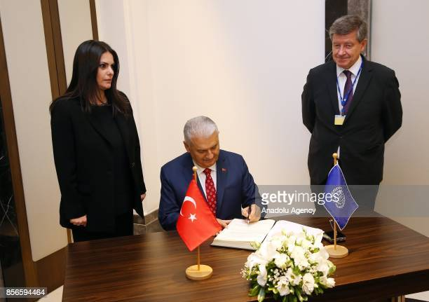 Turkish Prime Minister Binali Yildirim signs a guestbook of the International Labour Organization with DirectorGeneral of the International Labour...