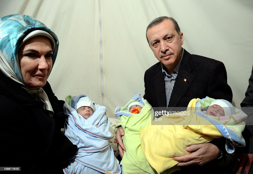 Turkish Prime Minister Recep Tayyip Erdogan (R) and his wife Emine Erdogan (L) hold babies as they visit Akcakale Refugee camp on December 30, 2012, in Urfa. International peace envoy for Syria Lakhdar Brahimi warned today in Cairo the Syrian war was worsening 'by the day' as he announced a peace plan he believed could find support from world powers, including key Syria ally, Russia. AFP PHOTO/STR