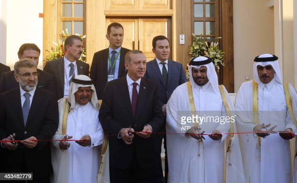 Turkish Prime Minister Recep Tayyip Erdogan cuts the ribbon during the opening ceremony of the new Turkish Embassy building in the Qatari capital...