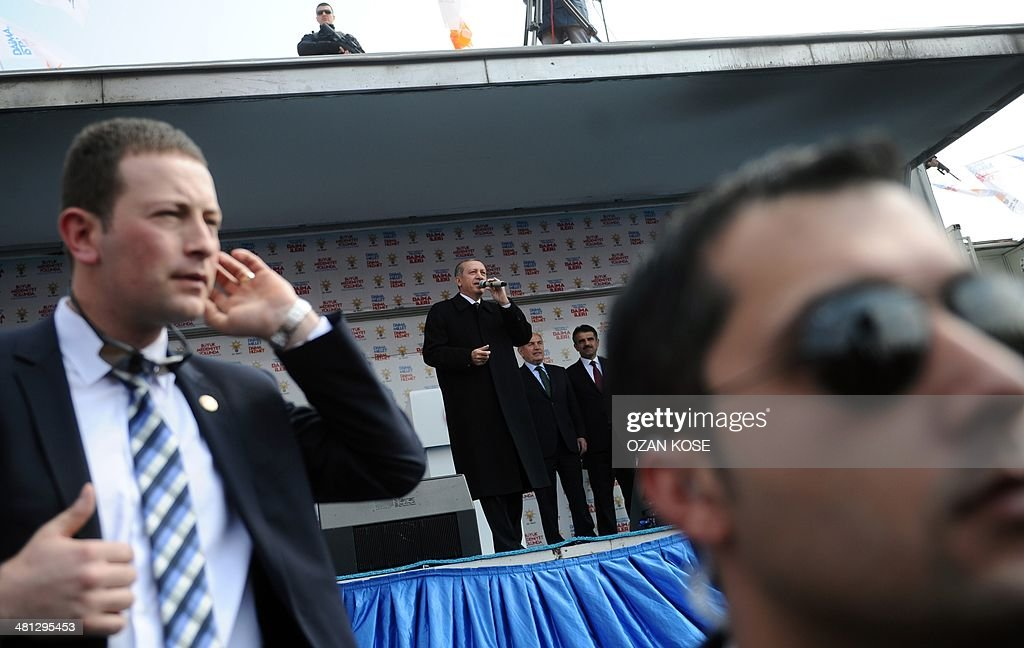Turkish Prime Minister Recep Tayyip Erdogan (C) delivers a speech while security police stand guard during a rally of the Justice and Development Party in the Kartal district at the asia side of Istanbul on March 29, 2014. Turkey gears up for local elections on March 30 ahead of a presidential vote in six months and parliamentary polls next year. Erdogan and his Islamic-leaning party, after over a decade in power, face the first electoral test following months of political turmoil, with mass street protests and a corruption scandal spread via Twitter, Facebook and YouTube. Amid an atmosphere of distrust ahead of tomorow's election with over 50 million eligible voters, the CHP and tens of thousands of citizen volunteers plan to monitor the ballot count.