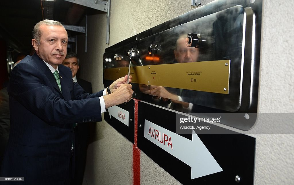 Turkish Prime Minister Recep Tayyip Erdogan fastens a board next to the red line representatively connecting Europe and Asia, after the inauguration ceremony of the Marmaray, the railway tunnel underneath the Bosphorus Strait linking European and Asian sides of Istanbul, on October 29, 2013 Istanbul, Turkey.