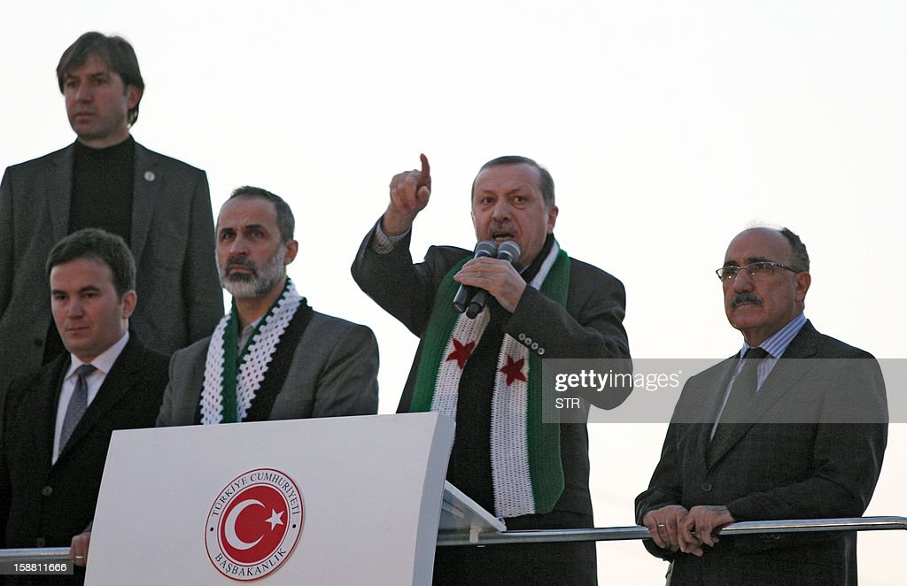 Turkish Prime Minister Recep Tayyip Erdogan (2ndR) flanked by with President of the National Coalition for Syrian Revolutionary and Opposition Forces Ahmed Moaz al-Khatib (3rdR) speaks to the audience during a meeting at Akcakale Refugee camp on December 30, 2012, in Urfa. International peace envoy for Syria Lakhdar Brahimi warned that the Syrian war was worsening 'by the day' as he announced a peace plan he believed could find support from world powers, including key Syria ally, Russia. AFP PHOTO/STR
