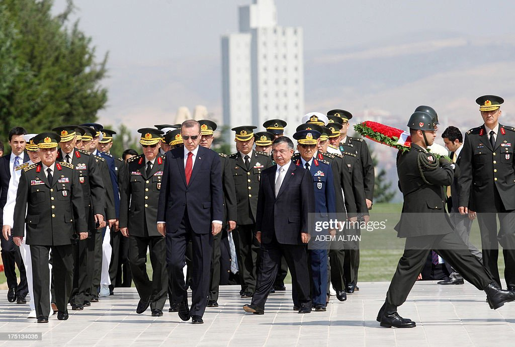 Turkish Prime Minister Recep Tayyip Erdogan (C) follows a military honour guard at the mausoleum of Mustafa Kemal Ataturk, founder of modern Turkey, before a meeting of the High Military Council in Ankara on August 1, 2013.