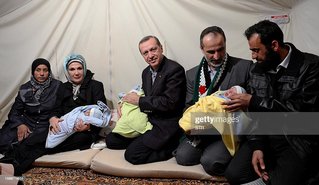 Turkish Prime Minister Recep Tayyip Erdogan (C), his wife Emine Erdogan (L) and President of the National Coalition for Syrian Revolutionary and Opposition Forces Ahmed Moaz al-Khatib (2ndR) hold babies as they visit Akcakale Refugee camp on December 30, 2012, in Urfa. International peace envoy for Syria Lakhdar Brahimi warned today in Cairo that the Syrian war was worsening 'by the day' as he announced a peace plan he believed could find support from world powers, including key Syria ally, Russia. AFP PHOTO/STR