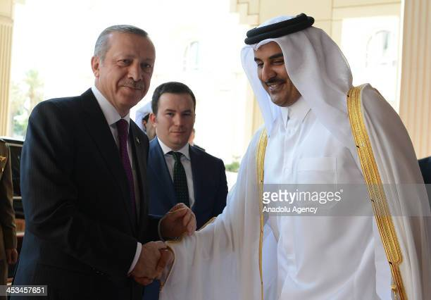 Turkish Prime Minister Recep Tayyip Erdogan shakes hand with Qatar's Emir Sheikh Tamim bin Hamad alThani as part of his Doha visit on December 4 2013...