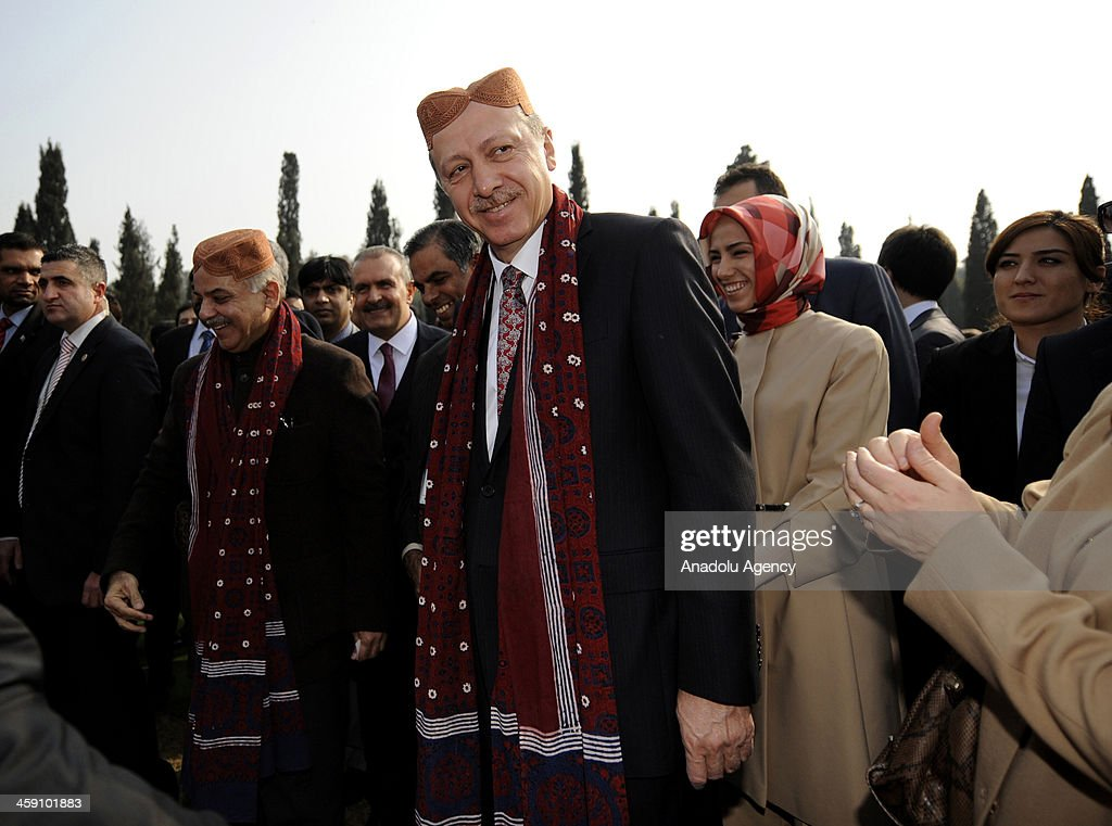 Turkish Prime Minister Recep Tayyip Erdogan visits the Grand Cultural Show as he wears a traditional cap that was given as a present by the Chief Minister of Pakistan's Punjab Province, Shahbaz Sharif (2nd L) in Lahore, Pakistan on December 23, 2013.