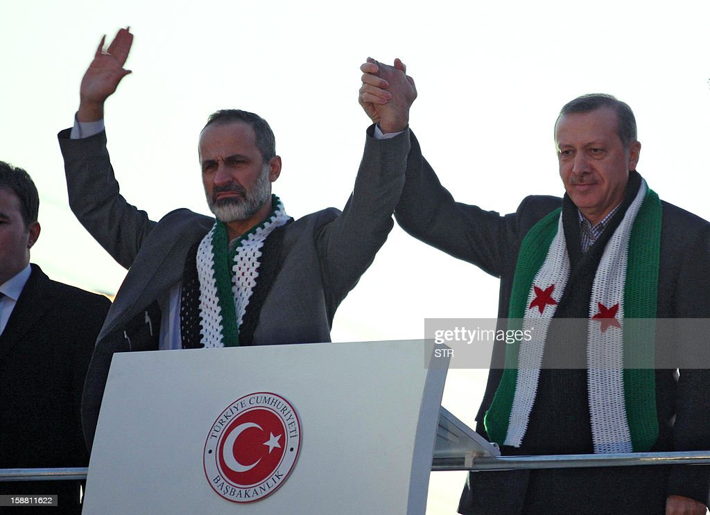 Turkish Prime Minister Recep Tayyip Erdogan (R) waves the audience with President of the National Coalition for Syrian Revolutionary and Opposition Forces Ahmed Moaz al-Khatib during a meeting at Akcakale Refugee camp on December 30, 2012, in Urfa. International peace envoy for Syria Lakhdar Brahimi warned today in Cairo that the Syrian war was worsening 'by the day' as he announced a peace plan he believed could find support from world powers, including key Syria ally, Russia. AFP PHOTO/STR