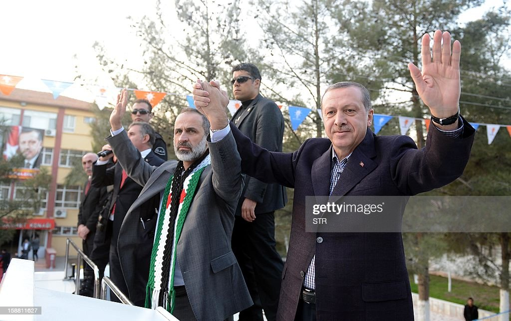 Turkish Prime Minister Recep Tayyip Erdogan (R) waves the audience with President of the National Coalition for Syrian Revolutionary and Opposition Forces Ahmed Moaz al-Khatib (C)during a meeting at Akcakale Refugee camp on December 30, 2012, in Urfa. International peace envoy for Syria Lakhdar Brahimi warned today in Cairo that the Syrian war was worsening 'by the day' as he announced a peace plan he believed could find support from world powers, including key Syria ally, Russia. AFP PHOTO/STR