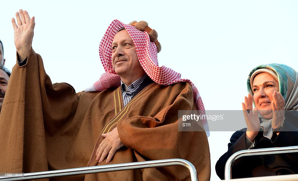 Turkish Prime Minister Recep Tayyip Erdogan (L) wearing arabic traditional clothes, waves the audience during a meeting at Akcakale Refugee camp on December 30, 2012, in Urfa. International peace envoy for Syria Lakhdar Brahimi warned today in Cairo that the Syrian war was worsening 'by the day' as he announced a peace plan he believed could find support from world powers, including key Syria ally, Russia.