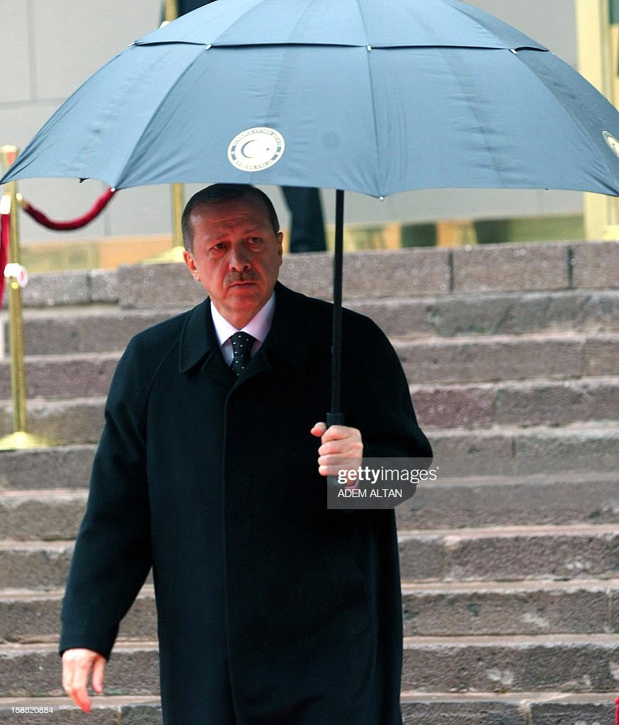 Turkish Prime Minister Tayyip Erdogan walks in the rain to welcome his Portuguese counterpart Passos Coelho in Ankara, on December 18 2012.