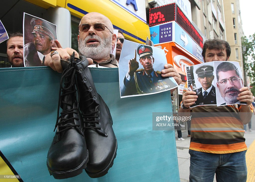 Turkish pro-Islamists demonstrate with military boots they plan to send to the US President Barack Obama (on poster at center) and to the European Union in protest for their alleged supports to the ousting of Egyptian President Mohammed Morsi (on poster at right) in Ankara, on July 17, 2013. AFP PHOTO / ADEM ALTAN