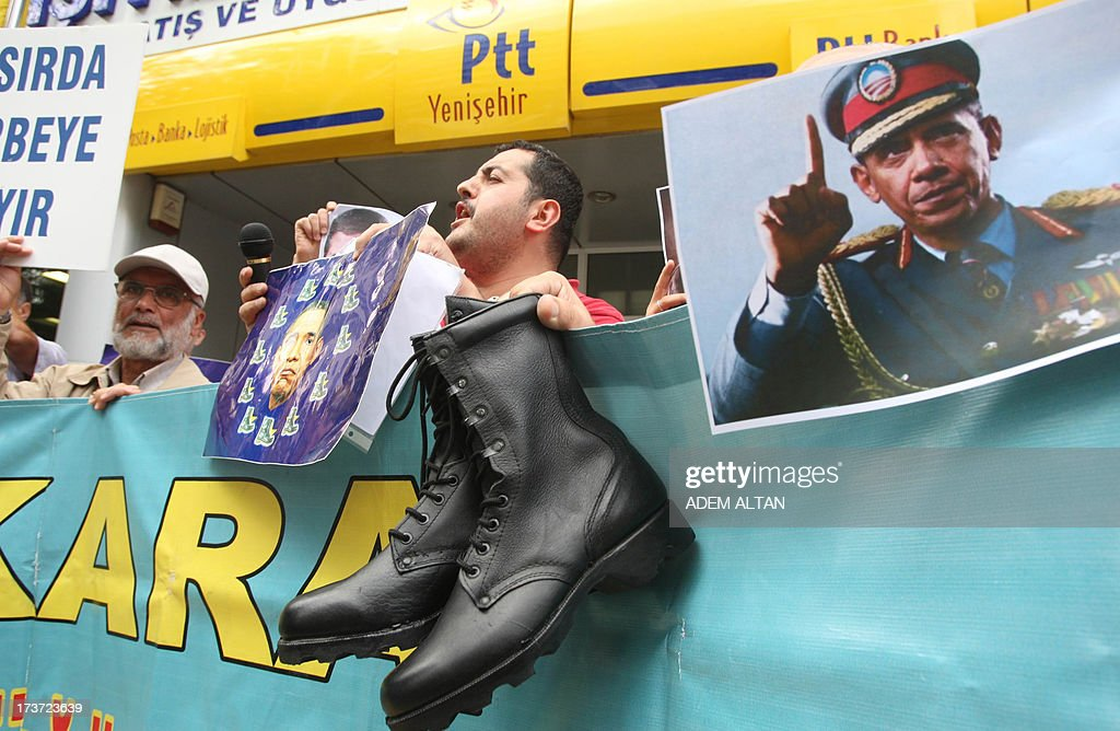 Turkish pro-Islamists demonstrate with military boots they plan to send to the US President Barack Obama (on poster at center) and to the European Union in protest for their alleged supports to the ousting of Egyptian President Mohammed Morsi in Ankara, on July 17, 2013. AFP PHOTO / ADEM ALTAN