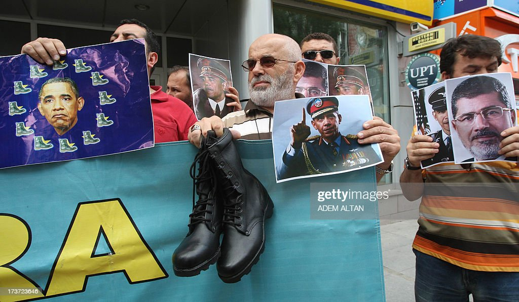 Turkish pro-Islamists demonstrate with military boots they plan to send to the US President Barack Obama (on poster at center) and to the European Union in protest for their alleged supports to the ousting of Egyptian President Mohammed Morsi (on poster at right) in Ankara, on July 17, 2013.