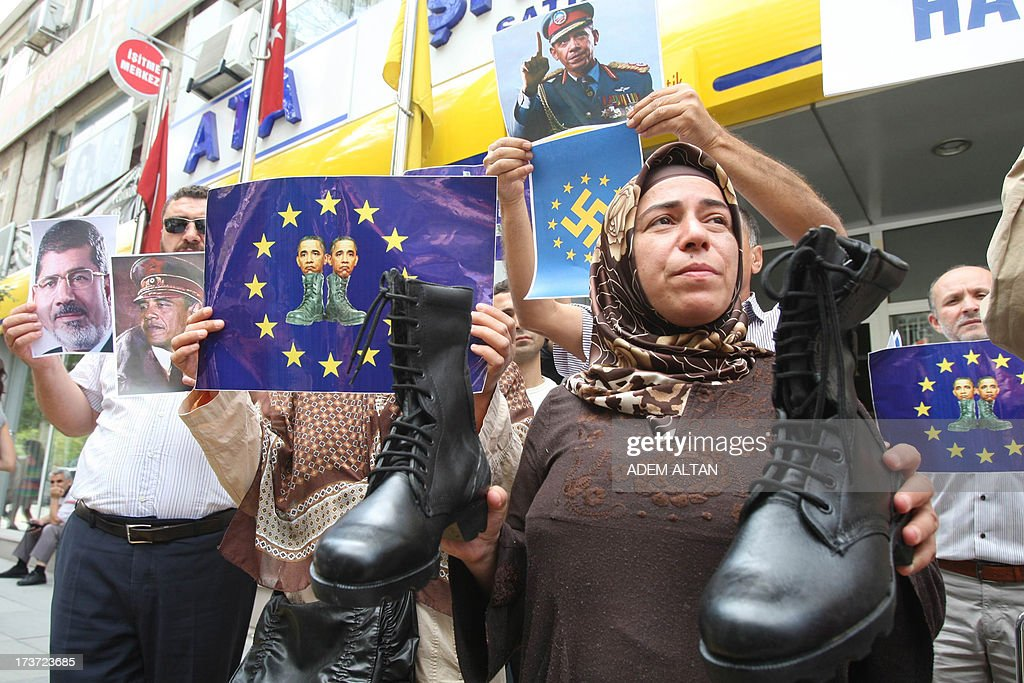 Turkish pro-Islamists demonstrate with military boots they plan to send to the US President Barack Obama (on poster on top) and to the European Union in protest for their alleged supports to the ousting of Egyptian President Mohammed Morsi (on poster at left) in Ankara, on July 17, 2013.