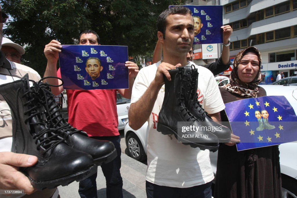 Turkish pro-Islamists demonstrate with military boots they plan to send to the US President Barack Obama (on poster) and to the European Union in protest for their alleged supports to the ousting of Egyptian President Mohammed Morsi in Ankara, on July 17, 2013. AFP PHOTO / ADEM ALTAN