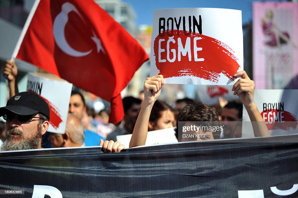 A Turkish protester holds a sign that reads 'Don't Obey' as anti-regime demonstrators march to the district of Kadikoy in Istanbul on September 15, 2013. Several people have been killed in clashes with riot police since demonstrations against the government of Prime Minister Recep Tayyip Erdogan, seen as increasingly authoritarian, began in June. AFP PHOTO/OZAN KOSE
