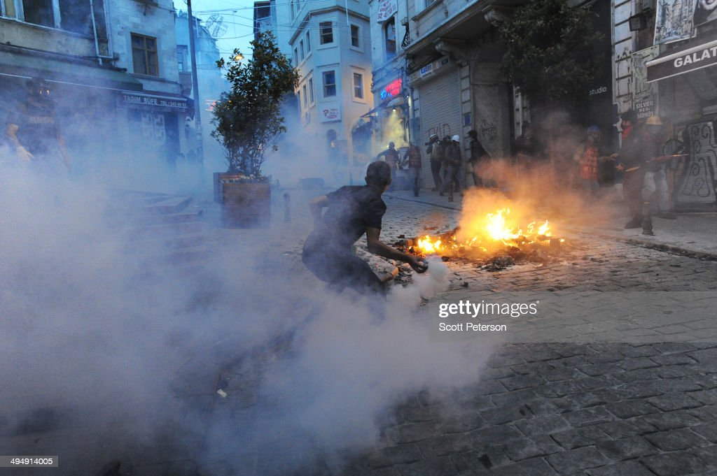 A Turkish protester throws a tear gas canister back at police amid protests to mark the one-year anniversary of the Gezi Park protests on May 31, 2014 in Istanbul, Turkey. The original protest over the removal of trees to convert a downtown park into a shopping mall turned into a broader, month-long protest against the authoritarian rule of Turkish Prime Minister Recep Tayyip Erdogan, presenting the political biggest challenge to the PM and his ruling AK Party (AKP) after more than a decade in power.