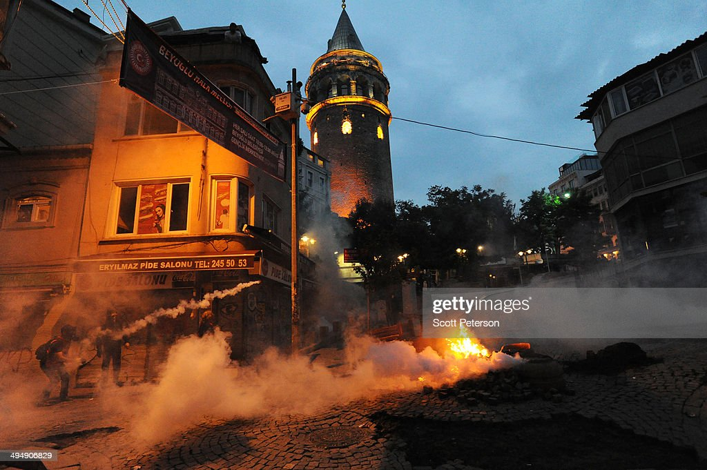 A Turkish protester throws a tear gas canister back at police beneath the Galata Tower amid protests to mark the one-year anniversary of the Gezi Park protests on May 31, 2014 in Istanbul, Turkey. The original protest over the removal of trees to convert a downtown park into a shopping mall turned into a broader, month-long protest against the authoritarian rule of Turkish Prime Minister Recep Tayyip Erdogan, presenting the political biggest challenge to the PM and his ruling AK Party (AKP) after more than a decade in power.
