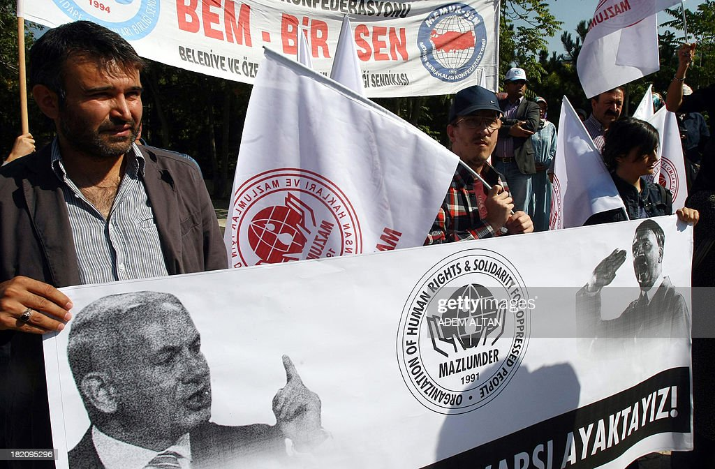 Turkish protesters hold a banner depicting Israeli Prime Minister Benjamin Netanyahu and Adolf Hitler and reading ''We stand against occupation of Jerusalem'', as they take part in a demonstration in front of the Israeli Embassy in Ankara on September 28, 2013. They protest against Israel's limitation of the attendance at al-Aqsa Mosque for Friday prayers and clashes in the past weeks over access to the Harim el-Sharif (The Noble Sanctuary), or Temple Mount. AFP PHOTO / ADEM ALTAN