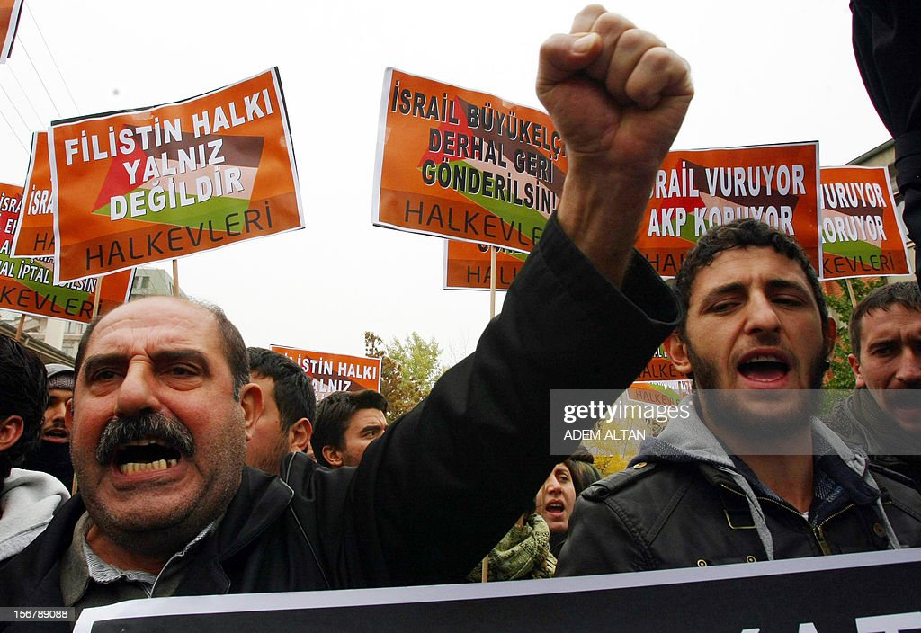 Turkish protesters hold a banner that reads ' Palestinian people are not alone ' during a demonstration against Israel's attack on Gaza outside the Israeli embassy in Ankara, November 21, 2012. urkish Prime Minister Recep Tayyip Erdogan on Tuesday accused Israel of 'ethnic cleansing' in Gaza, saying the Jewish state's air raids could not be considered self-defence. AFP Photo/ADEM ALTAN