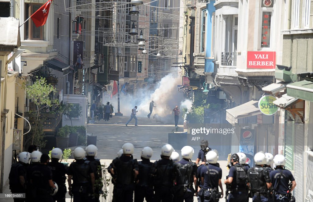Turkish protestors and riot policemen clash on June 1, 2013, during a protest against the demolition of Taksim Gezi Park, in Taksim Square in Istanbul. Police reportedly used tear gas to disperse a group, who were standing guard in Gezi Parki to prevent the Istanbul Metropolitan Municipality from demolishing the last remaining green public space in the centre of Istanbul as a part of a major Taksim renewal project. At least a dozen people were injured.