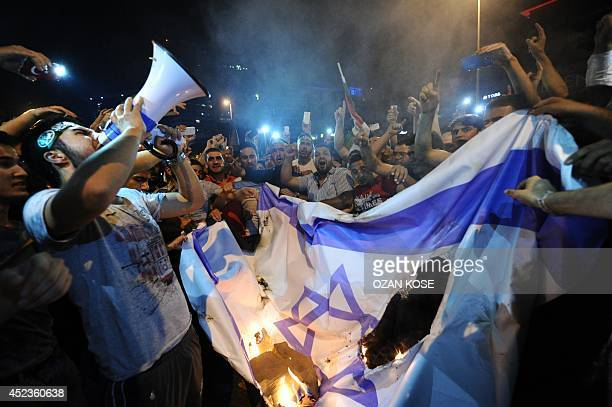 Turkish protestors set fire to Israel flag while they are shout slogans during a demonstration to denounce the Israeli military operations in Gaza on...