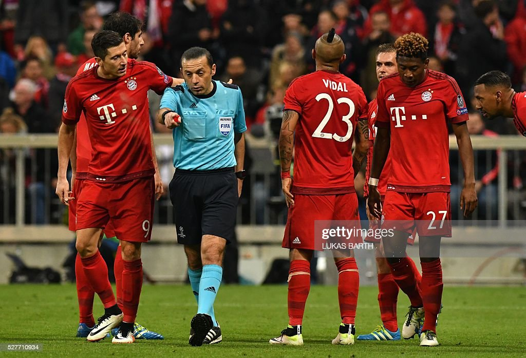 Turkish referee Cuneyt Cakir points to the penalty spot during the UEFA Champions League semi-final, second-leg football match between FC Bayern Munich and Atletico Madrid in Munich, southern Germany, on May 3, 2016. / AFP / LUKAS