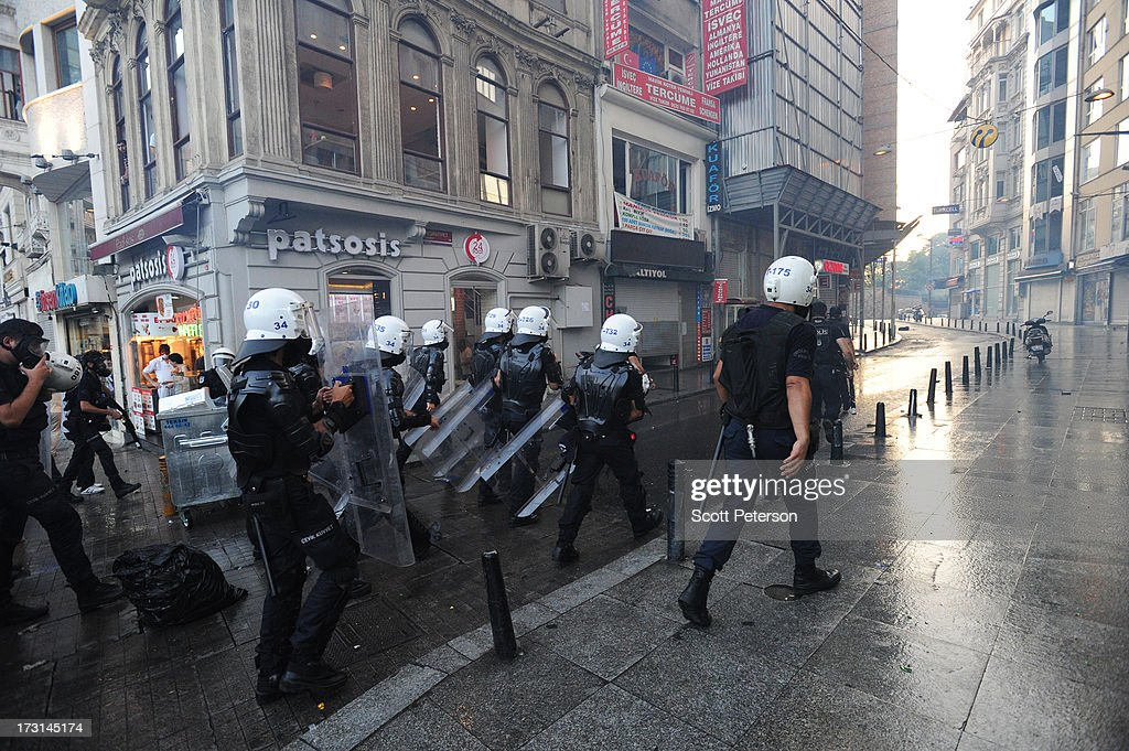 Turkish riot police advance as they battle anti-government protestors along the Istiklal shopping street near Taksim Square on July 8, 2013 in Istanbul, Turkey. The protests began in late May over the Gezi Park redevelopment project and saving the park trees adjacent to Taksim Square but swiftly turned into a protest aimed at Prime Minister Recep Tayyip Erdogan and what protestors call his increasingly authoritarian rule. The protest spread to dozens of cities in Turkey, in secular anger against Mr. Erdogan and his Islam-rooted Justice and Development Party (AKP).