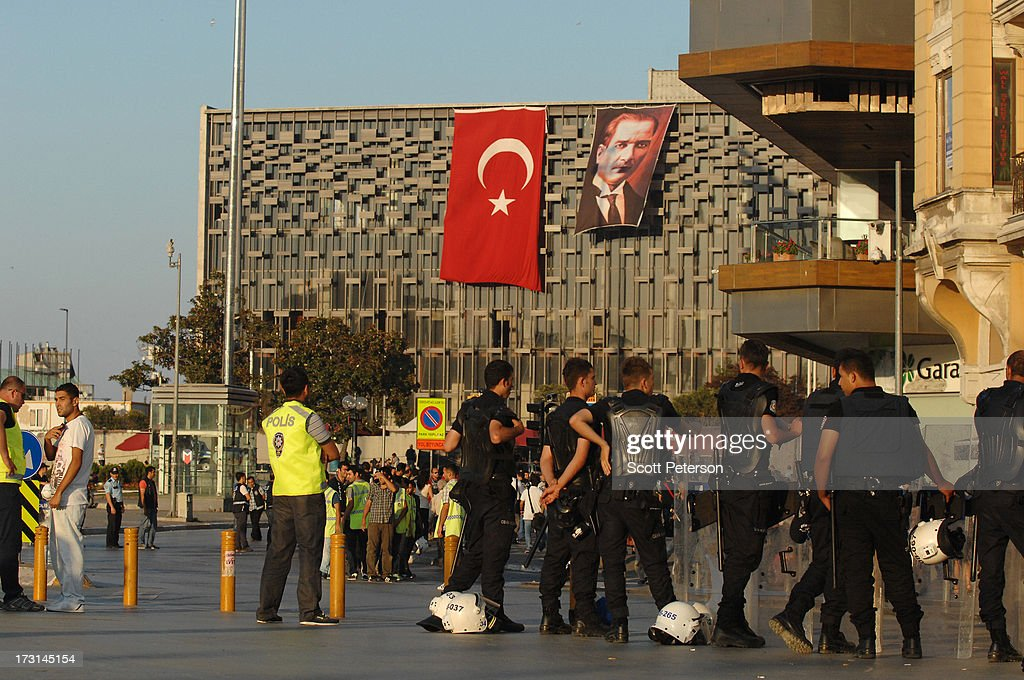 Turkish riot police line up in Taksim Square in front of a building with a Turkish flag and portrait of the founder of modern Turkey, Mustafa Kemal Ataturk, in Taksim Square on July 8, 2013 in Istanbul, Turkey. The protests began in late May over the Gezi Park redevelopment project and saving the park trees adjacent to Taksim Square but swiftly turned into a protest aimed at Prime Minister Recep Tayyip Erdogan and what protestors call his increasingly authoritarian rule. The protest spread to dozens of cities in Turkey, in secular anger against Mr. Erdogan and his Islam-rooted Justice and Development Party (AKP).