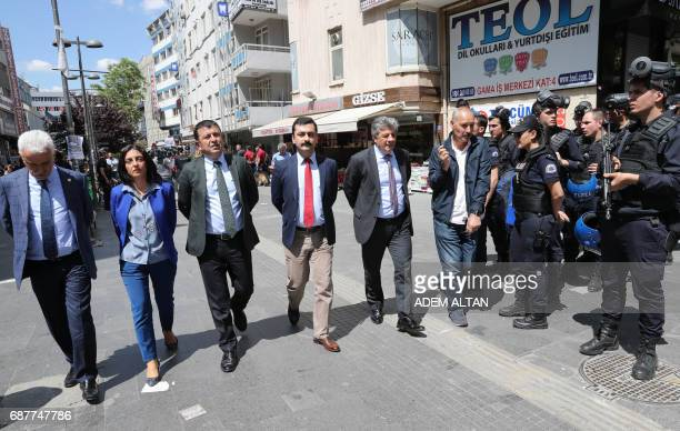 Turkish riot police look on as MPs from Turkey's main opposition party the Republican People's Party walk along a street as they protest against the...