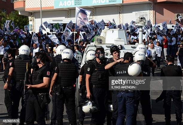 Turkish riot police stand guard opposite protesters in Diyarbakir on August 1 2015 during a demostration against jailed Kurdish leader Abdullah...