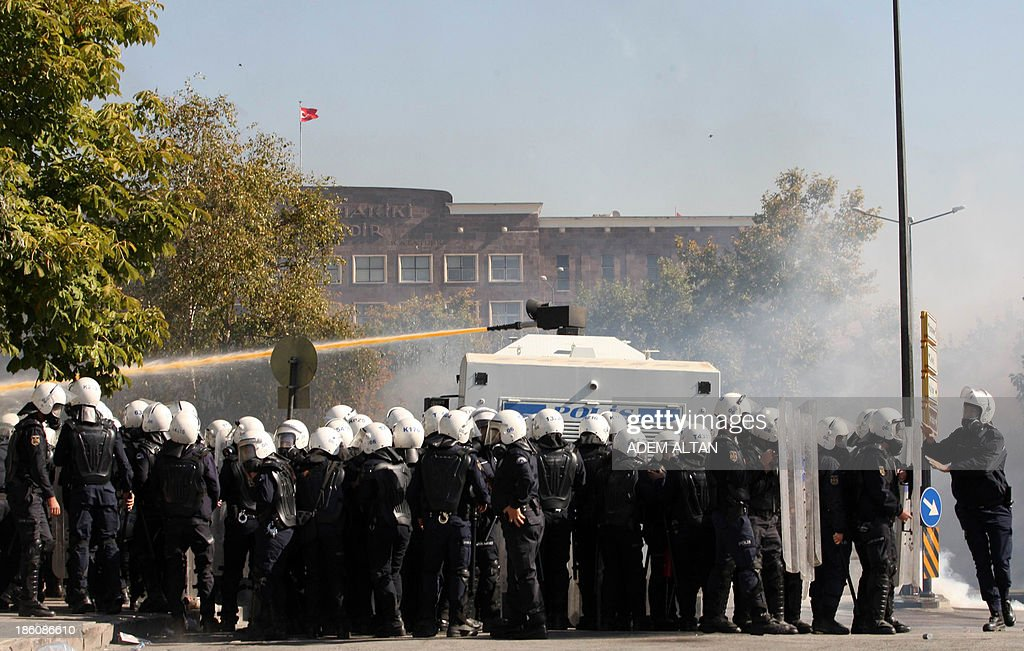 Turkish riot police take position while firing a water cannon to disperse protesters on October 28, 2013 during a demonstration in Ankara against a court's refusal to detain a policeman accused of killing a demonstrator during the popular unrest in June. A police officer identified only as Ahmet S. is on trial accused of shooting to death 26-year-old Ethem Sarisuluk during mass anti-government street protests in Ankara in June. The Ankara court rejected a demand by the victim's lawyers that the defendant be detained and ruled instead that he could take part in hearings via video conference for security reasons.