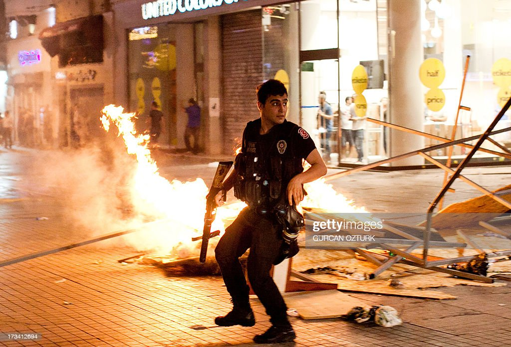 A Turkish riot policeman clashes with Turkish protestors on July 14, 2013 on Istiklal Avenue in the center of Istanbul. Turkish riot police fired rubber bullets, tear gas and water cannon to disperse hundreds of protesters trying to enter an Istanbul square that was the cradle of deadly unrest that engulfed the country in June. The police moved in when demonstrators protesting in the city's Beyoglu neighborhood against Prime Minister Recep Tayyip Erdogan moved toward nearby Taksim Square.