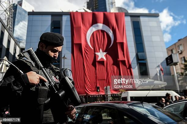 A Turkish riot policeman stands guard outside the headquarters of Bugun newspaper and Kanalturk television station in Istanbul during a protest...