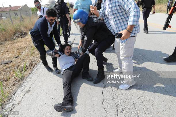 TOPSHOT Turkish riot policemen detain a protester during a court hearing of academic Nuriye Gulmen and teacher Semih Ozakca outside the Sincan prison...
