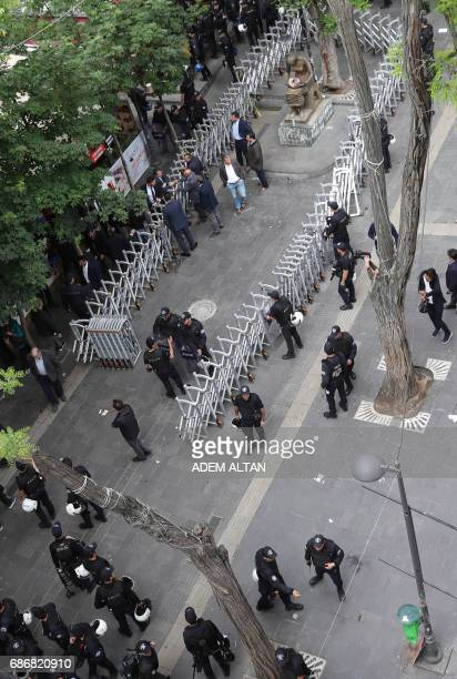 Turkish riot policemen stand next to barriers they have placed arround the Human Rights Monument during a demonstration against the arrest of hunger...