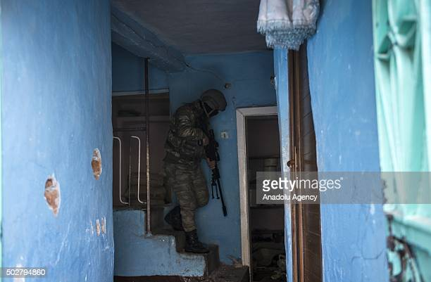 Turkish Security forces member walks down the stairs in a building as troops conduct counterterrorism operation in a neighbourhood under curfew for...