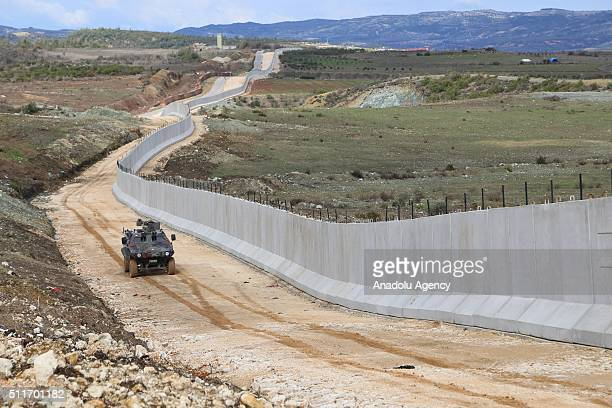 Turkish security forces patrol with an armored vehicle as 35 kilometres long 3 metres high and 7 tones weighted concrete wall builded in order to...