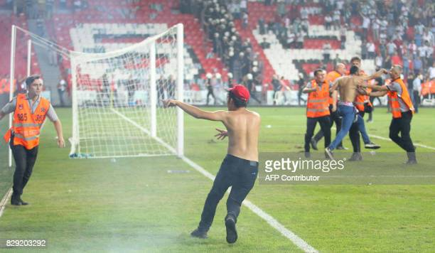 Turkish security officers try to detain football fans invading the pitch during the Turkish Super Cup final football match between Besiktas and...