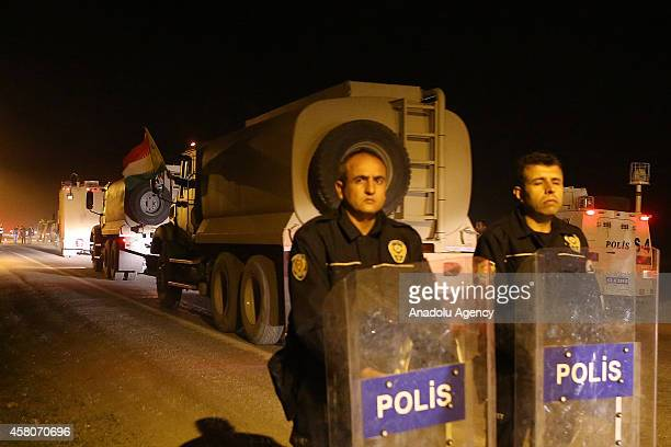 Turkish security officials take security measures as Iraqi Kurdish Peshmerga military convoy carrying heavy weapons belonging to Peshmerga forces...