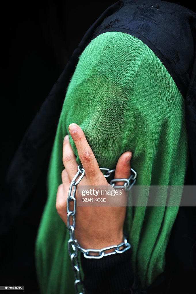 A Turkish Shiite woman holding a chain cries as she takes part in a religious procession held for the Shiite religious holiday of Ashura on November 13, 2013, in Istanbul. Ashura commemorates the killing of Imam Hussein, a grandson of the Prophet Mohammed, by armies of the caliph Yazid in 680 AD. Tradition holds that the revered imam was decapitated and his body mutilated in the Battle of Karbala.