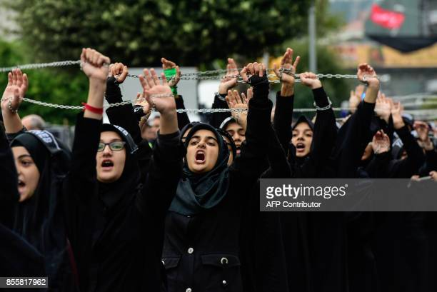 Turkish Shiite women hold up chains as they take part in a religious procession held for the Shiite religious holiday of Ashura on September 30 in...