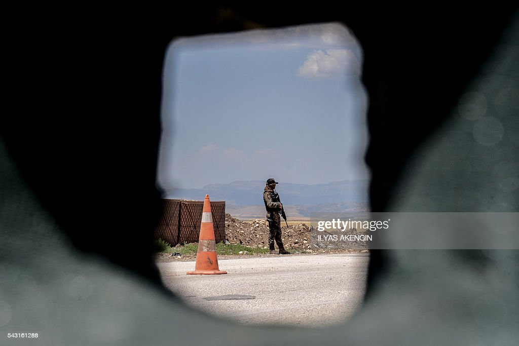 A Turkish soldier blocks the road at a military check point as Members of Parliament of the pro-Kurdish Peoples' Democratic Party (HDP) and kurdish activists wait in a military check point as they want to enter Lice district in Diyarbakir on June 26, 2016. Militants from the outlawed Kurdistan Workers Party (PKK) on June 24, 2016 killed six Turkish soldiers in two separate attacks in the troubled southeast of the country, the army said. / AFP / ILYAS